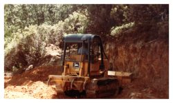 Image of a bulldozer next to a wall of dirt