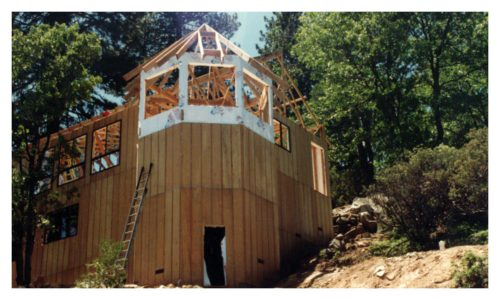 View of the house framing from below with open rafters and siding installed