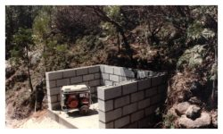 Image of a low u-shaped cinder block wall with an electric generator