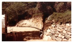 Image of flat graded area and dirt wall, rocks and a line of railroad ties