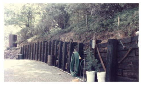 Image of completed railroad-tie retaining wall with old rusty tools hung on it