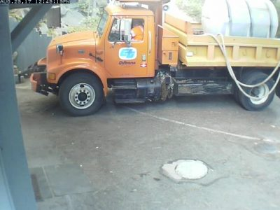 Image of a Caltrans tank truck in front of the house