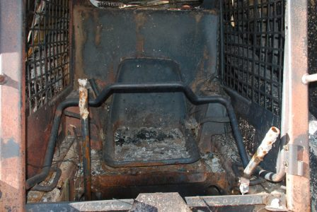 Image of a burned out Bobcat driver's seat and controls