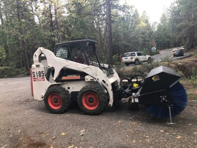 Image of a Bobcat skidsteer with angle broom attachment
