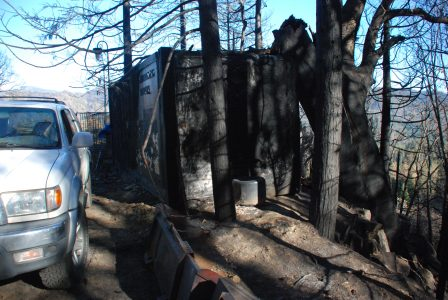 Image of a metal storage container surrounded by charred trees