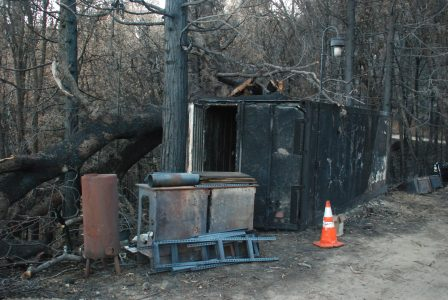 Image of several metal objects in front of a blackened metal storage container