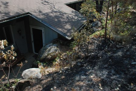 Image of a roof and door just below a blackened hillside