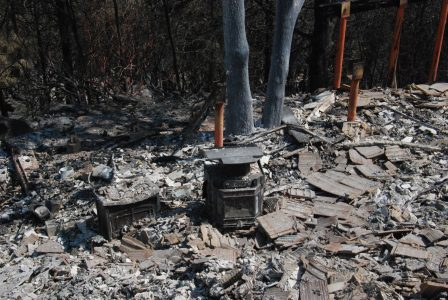Image of two burned out metal stoves resting on top of rubble