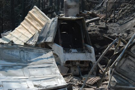 Image of a burned-out skidsteer amidst rubble