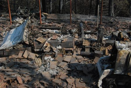 Image of concrete roofing tiles piled on top of burned out equipment