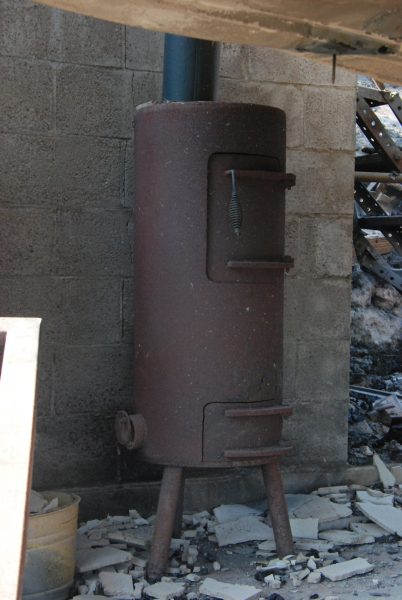 Image of a cast iron stove in front of a cinder block wall