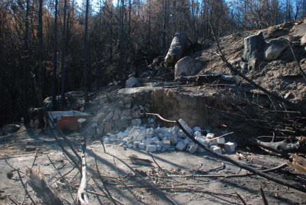 Image of a hillside with tree stump and cinderblock rubble below