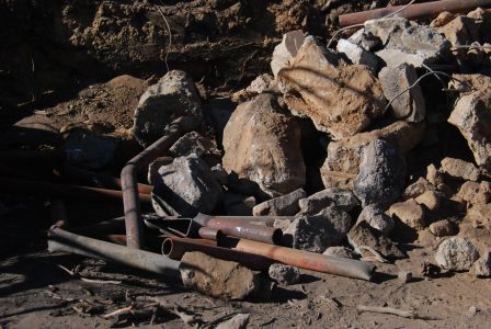 Image of bent metal tubes next to a pile large boulders