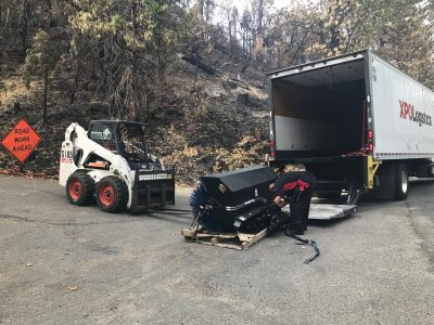 Image of a skidsteer picking up a pallet of heavy equipment
