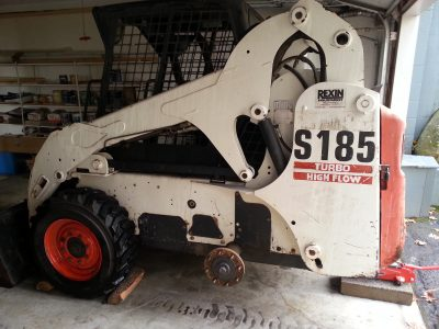Image of a Bobcat skidsteer with rear wheel removed