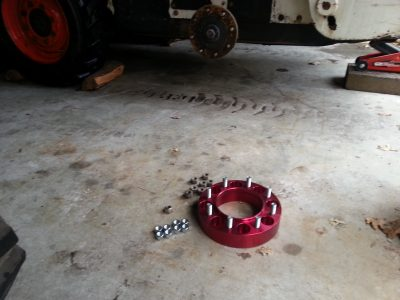 Image of a red aluminum wheel spacer next to the Bobcat