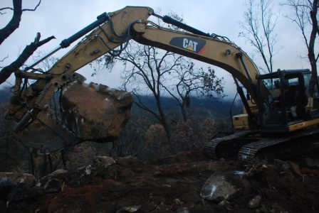 Image of a large boulder in the jaws of the excavator