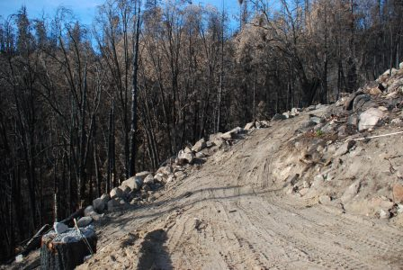 Image of a new dirt road edged with boulders