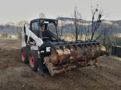 Image of a Bobcat skidsteer carrying several large logs with a grapple rake.