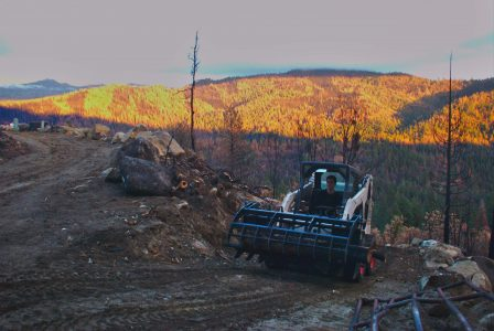 Image of the Bobcat carrying a load of logs, with the sunset lighting up the hills behind it