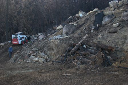 Image of the Bobcat driving up a steep road and a pile of logs in the foreground