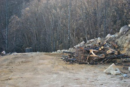 Image of a large pile of brush and wood on the otherwise empty space where the Logger's Retreat garage used to be