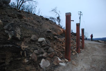 Image of the breezeway support posts and the bare hillside behind them