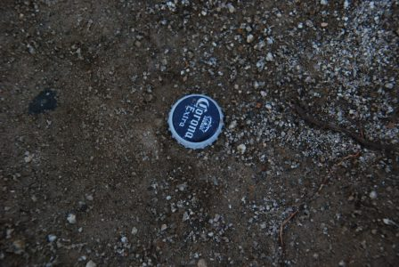 Image of a Corona Extra bottle cap in the dirt