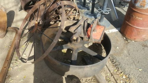 Image of a pile of rusted metal items including the flywheel