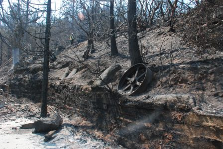 Image of a large cast iron flywheel resting on burned-out hillside