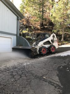 Image of Bobcat with brush attachment sweeping away slushy snow