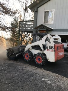 Image of Bobcat with brush attachment clearing snow in front of the house