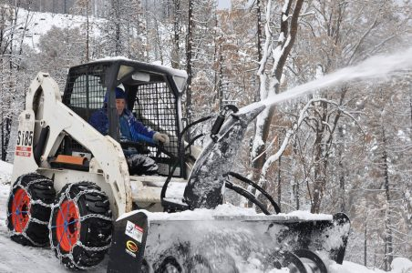 Image of Bobcat with snowblower attachment in action
