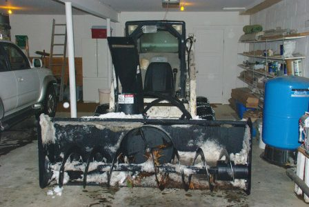 Image of Bobcat in the garage with fresh snow on the snowblower