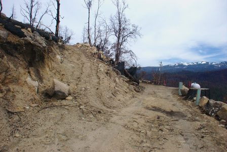 Image of a boulder blocking half of the dirt road
