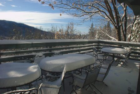 Image of snow-covered tables and chairs on the deck