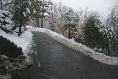 Image of a plowed driveway surrounded by about a foot of snow
