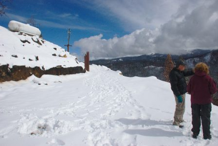 Image of the emply Logger's Retreat site with bright snow. blue sky, and dramatic clouds on ridgeline in the distance