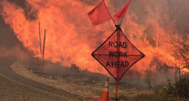 Large flames behind a Road Work Ahead sign