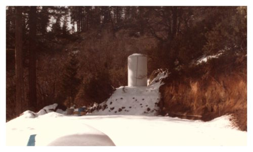 Image of a water tank next to the wall and snow on the ground
